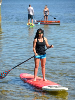 Paddle for Cancer participant Sharon Lord paddles around the Sabine Bay area Sunday.