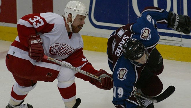 Detroit's Kris Draper gets his stick under the body of Colorado's Joe Sakic during 1st period action between the Detroit Red Wings and the Colorado Avalanche in Game 5 of the Western Finals Championships at Joe Louis Arena in Detroit, MI, May 27, 2002.