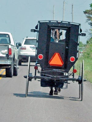 A truck passes an Amish buggy in Holmes County. According to an ODOT study, about 65% of collisions with buggies occur while passing.