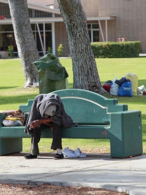 A homeless woman sits on a bench in Sunrise Park, a gathering spot for the homeless in Palm Springs, on December 1, 2016.
