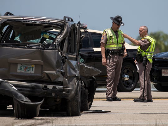 Florida Highway Patrol troopers inspect the scene of a fatal vehicle crash at the intersection of Michael G. Rippe Parkway and Briarcliff Road on Monday.