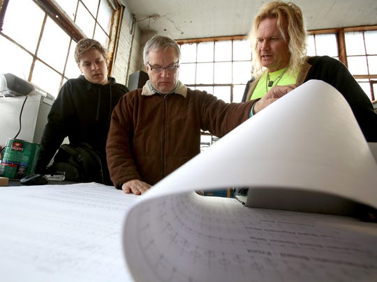 From left, Stuart McKay, 22, of Grosse Pointe, Covenant Organs owner Rick Helderop and woodworker Jamie Waggener, 53 of Pleasant Ridge look over organ blueprint plans as they figure out how to engineer and build new parts for one of the organs they are repairing on Tuesday, December 20, 2016.