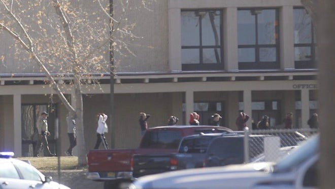 Students are led out of Aztec High School Thursday morning after a fatal shooting.