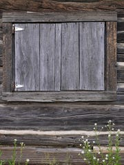A wooden door covers each window on the Rosenberger Pioneer Cabin, also known as the Rosenberger House.
