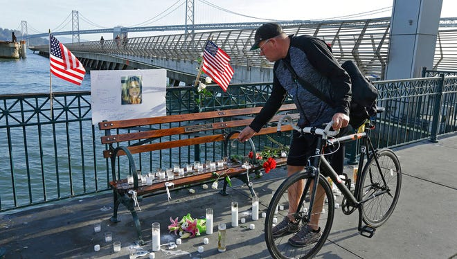Craig Warner of Palo Alto, Calif., leaves a bell at a memorial site for Kate Steinle on Pier 14 Friday, Dec. 1, 2017, in San Francisco.