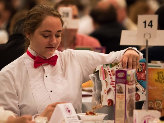 Hayleigh Duff, a student from St. Philip Catholic Central High School, eats cereal with her classmates at the 2015 Community Prayer Breakfast.