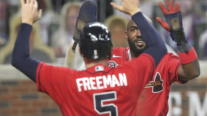 Atlanta Braves Marcell Ozuna (right) and Freddie Freeman celebrate after scoring on a 3-RBI double by Travis D'Arnaud that proved to be the game winner for an 11-10 lead over the New York Mets on Friday.