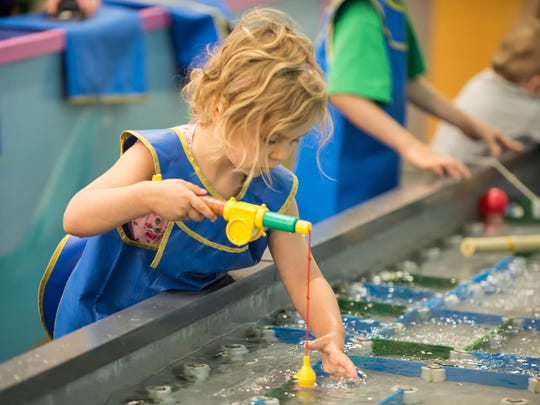 Four-year-old Daphne Willis from Battle Creek tries to catch a play fish at Kids 'N' Stuff in downtown Albion.