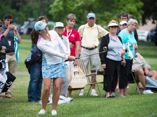 Spectators watch tournament winner Madeleine Sheils from Boise, Idaho chip onto no. 18 during the final day of the Symetra Tour at the Battle Creek Country Club on Sunday.