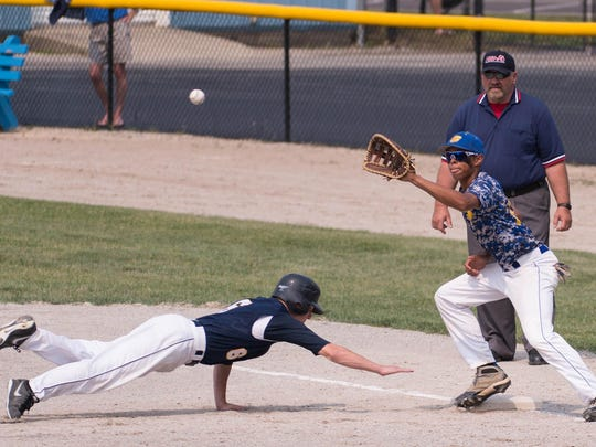 Climax-Scotts' Kyler Skidmore dives back to first base during the Division 4 state quarterfinal held at C.O. Brown on Tuesday.