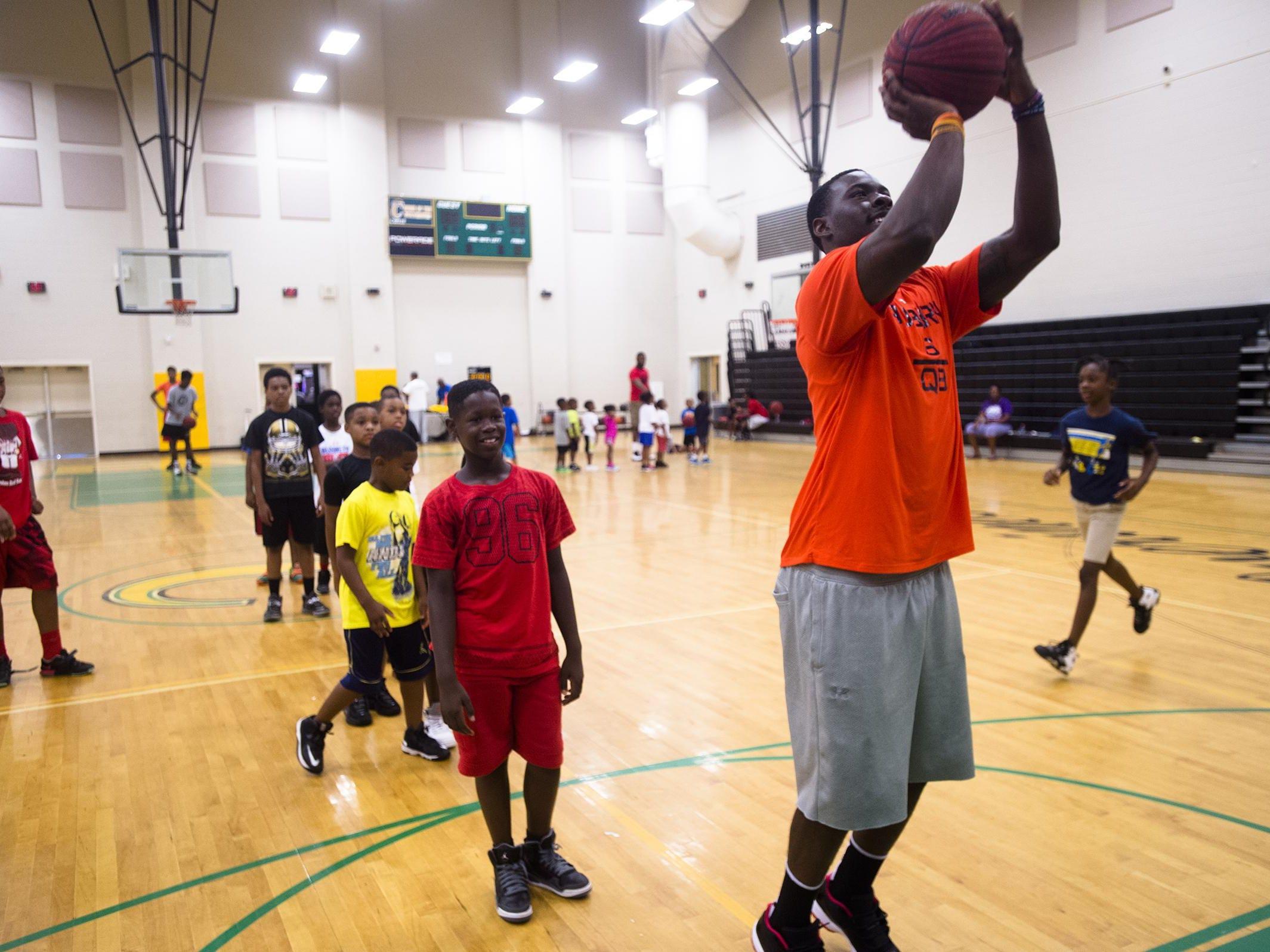 Jeremy Johnson, Auburn University quarterback, helps at the Carver High School basketball camp on Wednesday, July 8, 2015, in Montgomery, Ala.