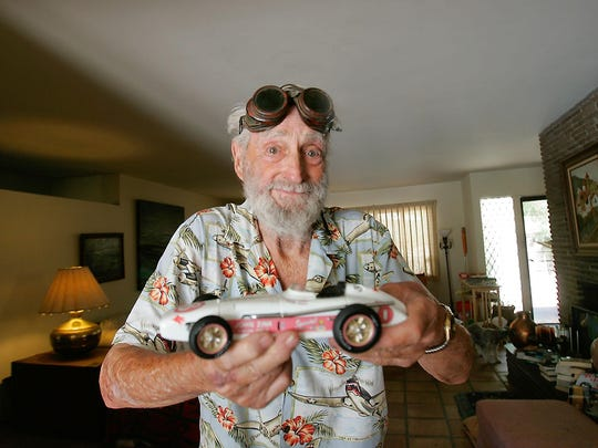 Donning the welder's goggles he wore when he built it, Bill Byrne holds a replica of the 1956 winning Indy 500 car that he designed and built.