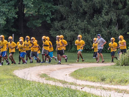 Battle Creek Central football players run to the practice field during their football camp at Clear Lake Camp.