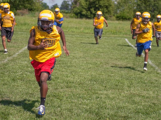 Battle Creek Central football players run sprints during football camp at Clear Lake Camp.