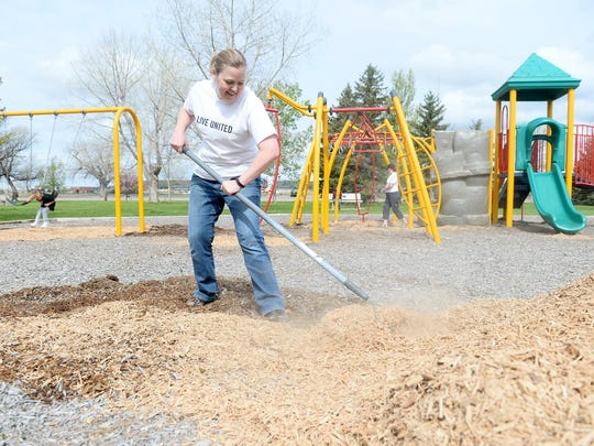 Kim Skornogoski of the United Way spreads new wood shavings at the playground in Elk's Riverside Park on Saturday.