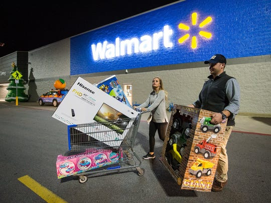Two people with products in front of a Walmart store.