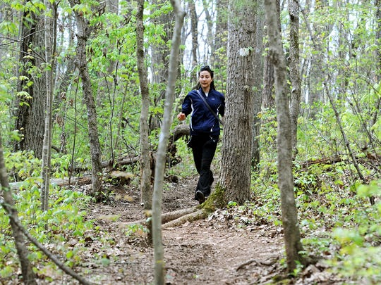Stephany Nezo runs on a trail with her dog, Pax, following behind her as they enjoy an area of the Blue Ridge Parkway near the Folk Art Center on Wednesday. Nezo says she hikes often with her dog.