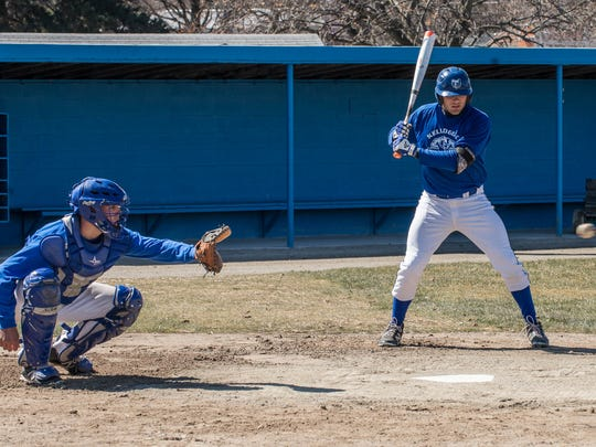 KCC baseball players Alex Goodwin catches while Alex