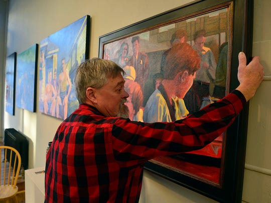 Steven Carlyle Smith hangs his oil paintings at Portal Gallery on Tuesday, ahead of the First Friday Art Walk.