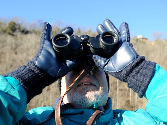 A bird watcher scouts the skies over Bull Shoals Lake
