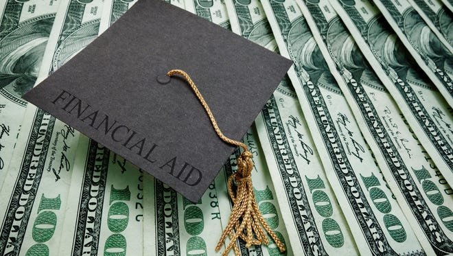 graduation cap with Financial Aid text on assorted hundred dollar bills