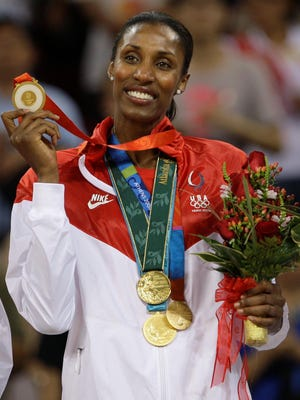 USA player Lisa Leslie holds up the fourth of her gold medals after receiving gold for beating Australia in the women's basketball gold medal game at the Beijing 2008 Olympics in Beijing,  Saturday, Aug. 23, 2008.