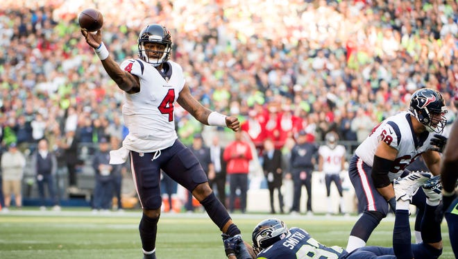 Houston Texans quarterback Deshaun Watson (4) throws a touchdown pass as he is tackled by Seattle Seahawks defensive end Marcus Smith (97) during the second half at CenturyLink Field.