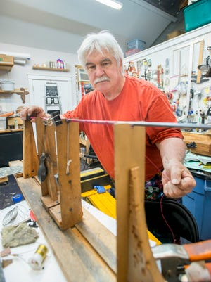 """Artist Greg Saunders demonstrates how he uses his """"spiralator 2000 wrapping machine"""" to wind wire around a stick that he uses in sculptures at his studio in Pensacola on Friday, May 26, 2017."""