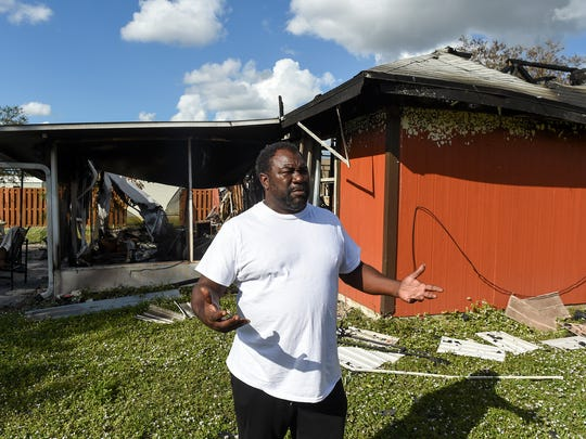 Standing in front of his house in Port St. Lucie Dec. 6, Gary Grimsley describes escaping his burning home on 2100 block of Monterrey Lane with his family. Grimsley, along with his wife, DeLacy Bembry, and their two children narrowly escaped the flames late in the evening of Dec. 3.