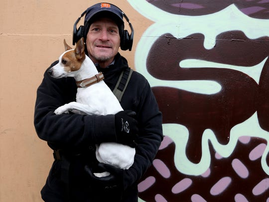 Rick Michael Stewart, 51 of Detroit with his dog Chica on Riopelle Street at Eastern Market in Detroit on Saturday, November 8, 2014. Stewart was biking around and stopped to talk about the ending of Detroit's Chapter 9 bankruptcy that happened the day before and going forward how it will affect the city.He moved back to the city of Detroit, living in Midtown, two years ago and is optimistic about the changes happening to the city with the current mayor Mike Duggan and the people he's surrounding himself with.