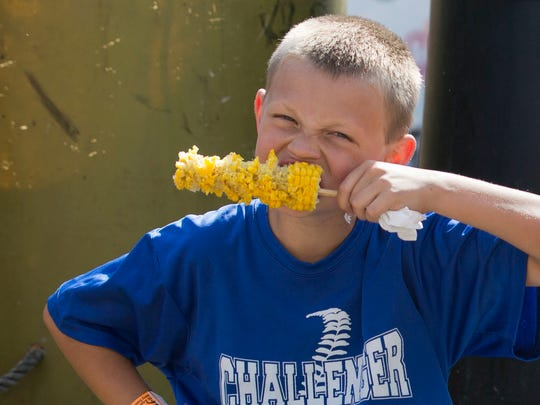 Zayden Kinsey, 10 chows down on some corn on the cob as he spends his day off of school with his dad, Brian, at the Fall Festival on Friday afternoon.
