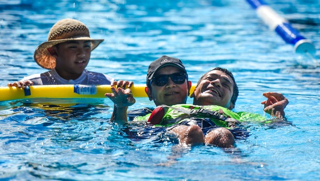 Special Olympian athlete David Wooten manages a smiles as he demonstrates his willingness to win as he nears the finish swimming in the 10-yard backstroke flotation assisted race at the 42nd annual Special Olympics Guam Aquatics event at the Hagåtña Pool on Saturday, June 9, 2018.