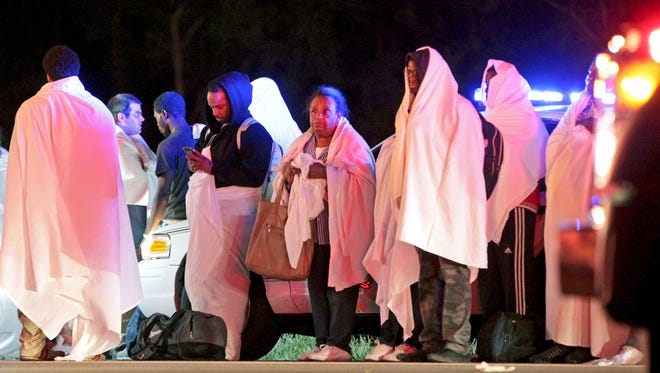 Passengers of an overturned Greyhound bus stand near the scene.