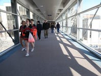 Le Mars community high school cheerleaders, Amani Boddie, Andrea Kommes and Raquel Yoerger walk through the skywalk on the first day of the state wrestling tournament on Thursday, Feb. 19, 2015 in Des Moines.