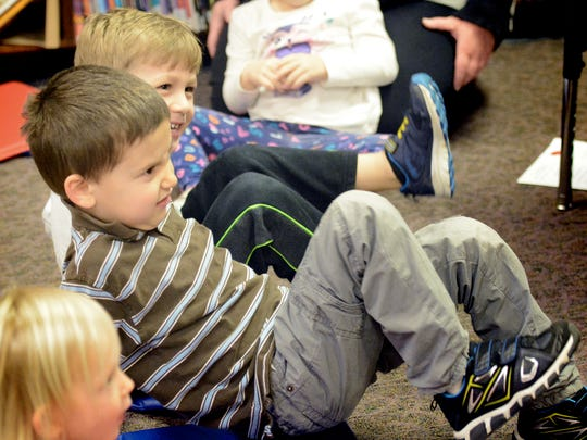 Ben Hamilton, 5, of Hallam, foreground, and Owen Steinkamp, 4, of Springettbury Township, stomp their feet to a song during a pre-school story time at Kreutz Creek Library in Hellam Township Friday, Feb. 16, 2018. Storyteller Felicia Gettle, a York County Library System employee, says her hours have been cut due to funding shortfalls. Bill Kalina photo