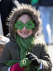 Emily McDonald, 6, is all smiles as she watches her dad march in the Pearl River St. Patrick's Day Parade on Sunday.