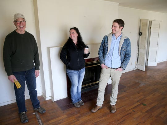 Brother and sister reals estate brokers Michael Bowes (right) and Bernadette Schuster of Strategy Real Estate take buyer Richard Sollom through a dilapidated home near Olympic College that he bought.
