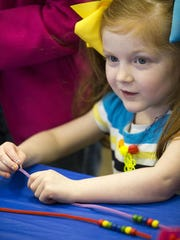 Kaylee Kempers, 4, Indianapolis, works on a simulated DNA double helix at Passport to Hi-Tech, at Conner Prairie in Fishers on Saturday, March 5, 2016.