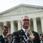 Jim Obergefell holds up a photo of his late husband, John Arthur, while speaking on the steps of the United States Supreme Court.