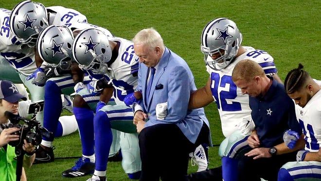 Los Cowboys de Dallas, liderados por el propietario del equipo, Jerry Jones, en el centro, se arrodillan antes del himno nacional previo a un partido de NFL contra los Cardinals de Arizona, el lunes 25 de septiembre de 2017, en Glendale, Arizona
