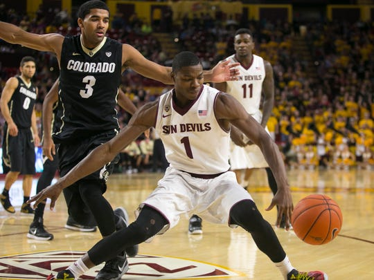ASU guard Roosevelt Scott struggles to maintain control of the basketball as Colorado's Xavier Talton looks on during the second half of a Pac-12 game at Wells Fargo Arena in Tempe on Saturday, January 17, 2015.