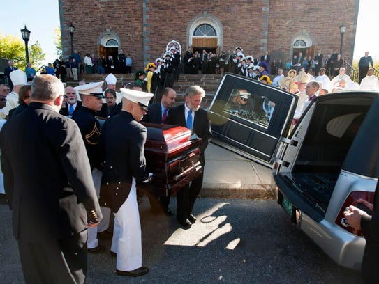 The casket is loaded into the hearse after funeral