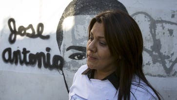 Araceli Rodriguez stands before a Nogales, Sonora, mural of her son, Jose Antonio Elena Rodriguez.