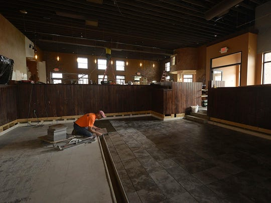 Bruce Butterfield, from Macco's Commercial Interiors, Inc., works on laying tile inside Leatherhead Brewing Company in Green Bay on Monday.