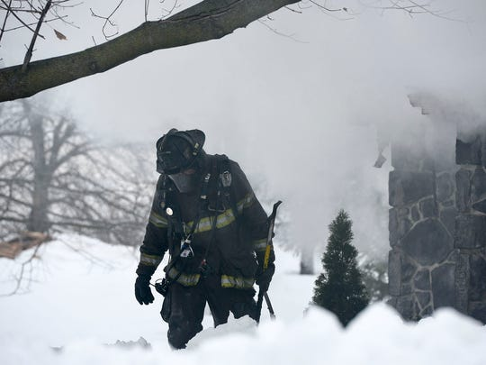 A fire fighter walks back toward a tree to take a break after going through a house full of smoke at 2528 Cider Road in Chambersburg, Pa. on Tuesday, 26, 2016.