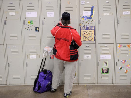 Laura Kaufman opens her locker at work on May 31, 2016, at Transitions North in Lansing. Laura earns a little more than $2 an hour doing simple, repetitive tasks alongside other workers with significant disabilities.