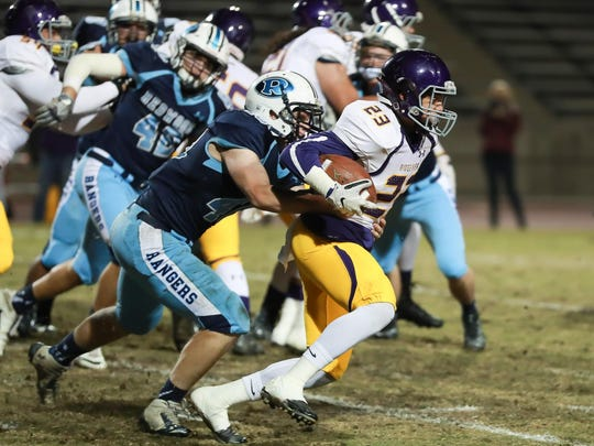 Ridgeview's Tye Johnson (23) attempts to break free from Redwood's Ryan Montemagni (40) in a Central Section Division II quarterfinal high school football game at Mineral King Bowl.