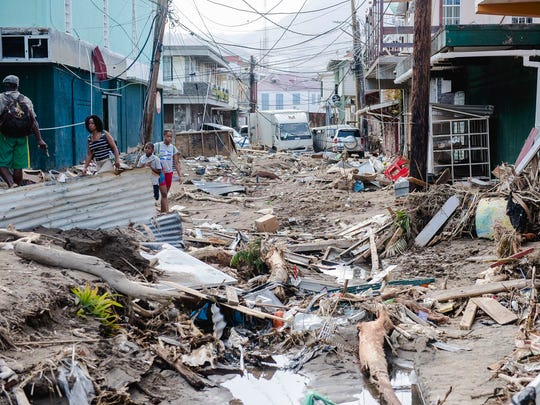 Residents stand amid rubble Sept. 22, 2017 in Roseau, capital of the Caribbean island Dominica, four days after the passage of Hurricane Maria.