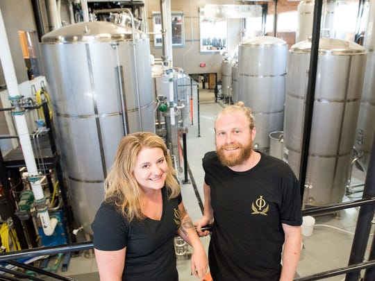 Head brewer Melissa Test and brewery-distillery co-owner Will Whipple pose in the Mill Street Still with towering fermenters behind them. The Mill Street Still and Brew opened over the summer and makes beer and vacuum distilled vodka.