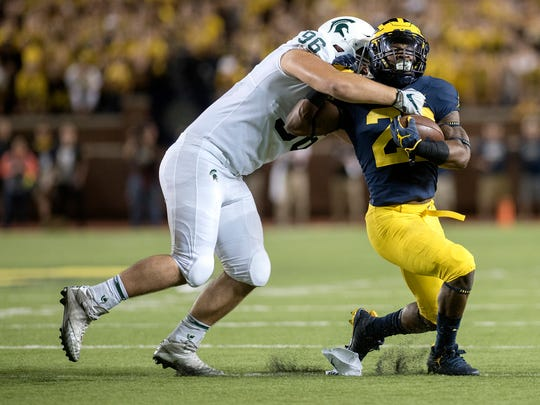 Michigan State's Jacub Panasiuk, left, tackles Michigan's Karan Higdon during the first quarter on Saturday, Oct. 7, 2017, at Michigan Stadium in Ann Arbor.